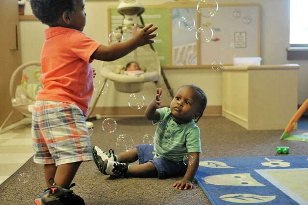 Quadir, left, 15 months, and Cassidy, 15 months try to catch bubbles in the infant room at the CEO Head Start program on Monday, July 20, 2015, in Troy, N.Y. Better access to early childhood programs is seen as a way to improve child well-being.  (Paul Buckowski / Times Union) Photo: PAUL BUCKOWSKI / 00032686A