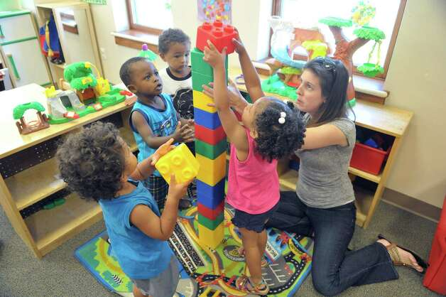 Children in the toddler room play with Kristin Breen, right, an Early Head Start staff member at the CEO Head Start program on Monday, July 20, 2015, in Troy, N.Y.  Breen also does educational home visits for children not in the day program.  Better access to early childhood programs is seen as a way to improve child well-being. (Paul Buckowski / Times Union) Photo: PAUL BUCKOWSKI / 00032686A