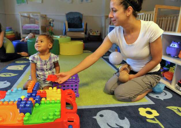 Shyenne, 16 months, plays with infant teacher, Ivelisse Rivera at the CEO Head Start program on Monday, July 20, 2015, in Troy, N.Y.  Better access to early childhood programs is seen as a way to improve child well-being.  (Paul Buckowski / Times Union) Photo: PAUL BUCKOWSKI / 00032686A