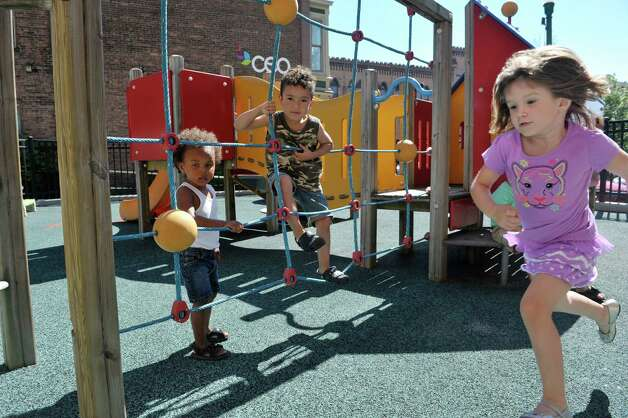 Amari, left, 3, Jayden, center, 3, and Lily play outside at the CEO Head Start program on Monday, July 20, 2015, in Troy, N.Y. Better access to early childhood programs is seen as a way to improve child well-being.  (Paul Buckowski / Times Union) Photo: PAUL BUCKOWSKI / 00032686A