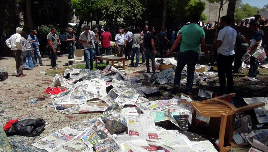 Dead bodies are covered by newspapers at the site of an explosion that killed tens of people and injured scores others is seen in the southeastern Turkish city of Suruc near the Syrian border, Turkey, Monday, July 20, 2015. A midday explosion in Turkey's southeastern city of Suruc near the Syrian border killed 28 people Monday and sent nearly 100 others to the hospital, Turkish officials said. The prime minister's office gave the casualty toll in a phone call to The Associated Press. There was no immediate claim of responsibility for the blast. (AP Photo) Photo: STR / ap