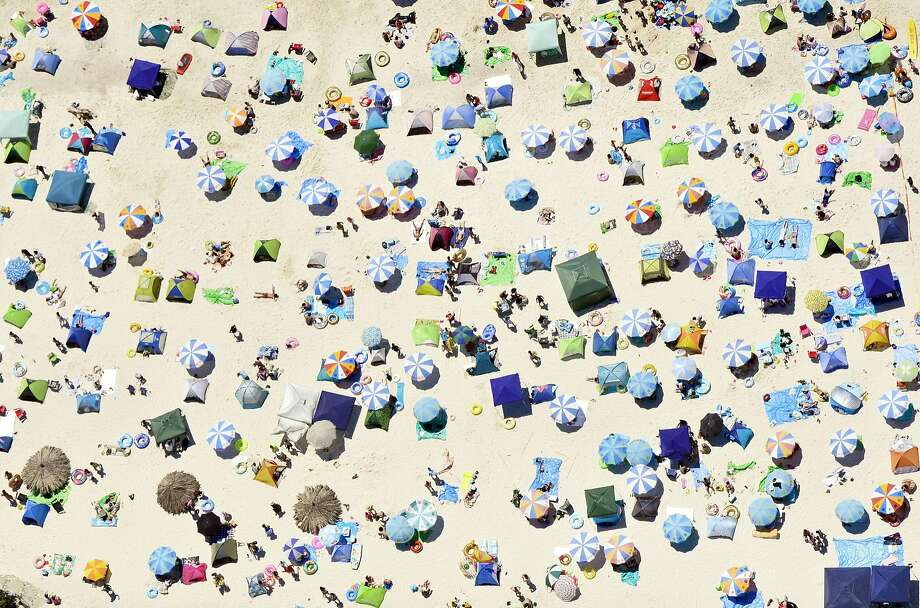 Umbrellas and beach-goers pack a beach in Shirahama town, Wakayama prefecture, western Japan on the Marine Day national holiday Monday, July 20, 2015. Photo: Associated Press