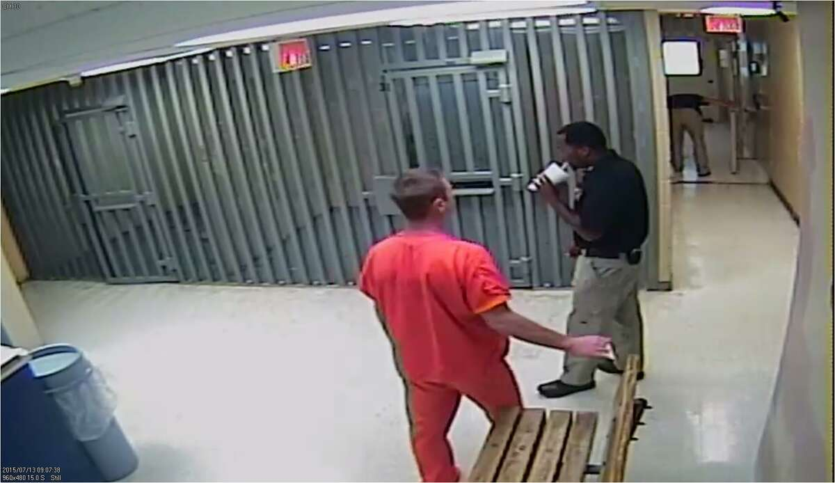 A female officer bends down, back right, to peer through the window of Sandra Bland's cell.