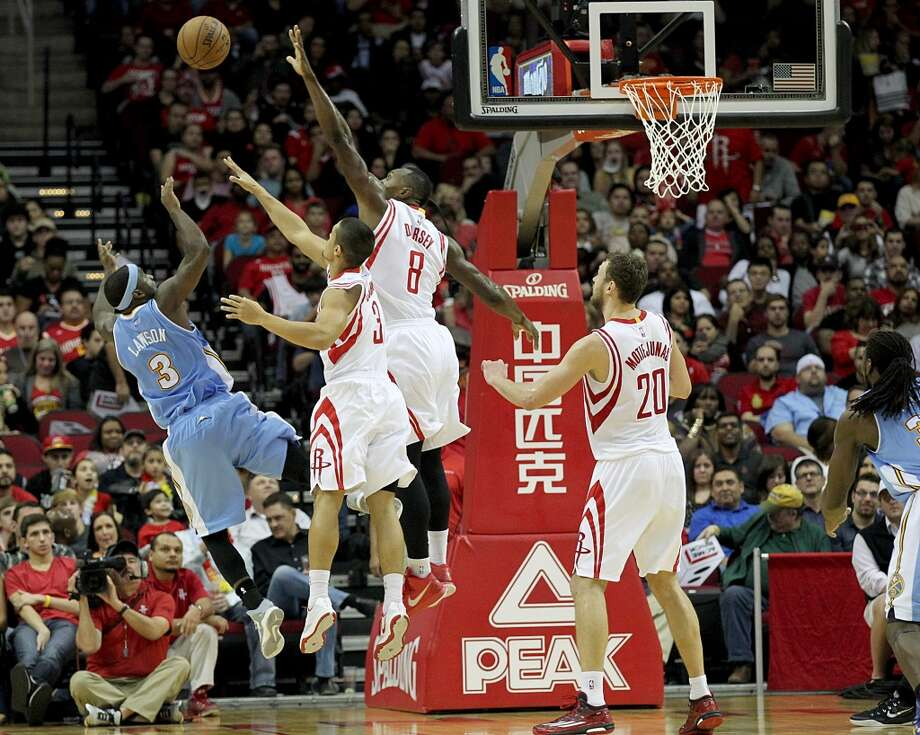 Houston Rockets guard Nick Johnson (3) and Houston Rockets forward Joey Dorsey (8) defend against Denver Nuggets guard Ty Lawson (3) shot in the second half at Toyota Center on Saturday, December 13, 2014 in Houston, TX. Rockets won 108 to 96.  (Photo: Thomas B. Shea/For the Chronicle) Photo: For The Chronicle