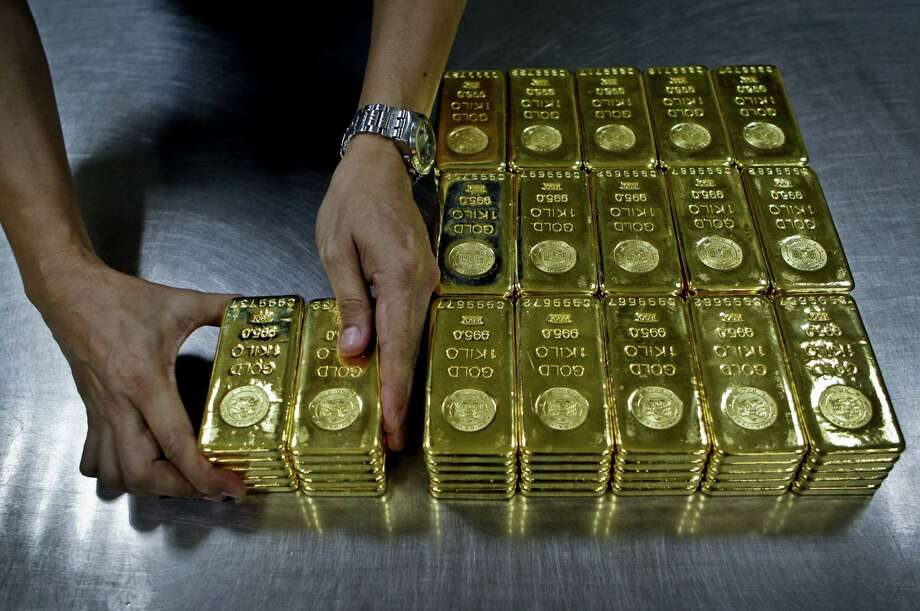 A technician prepares 1 kilogram gold bars for delivery at Emirates Gold in Dubai. Gold is going for $1,106 an ounce. In 2011 it was at nearly $1,900. Photo: Kamran Jebreili, STF / AP