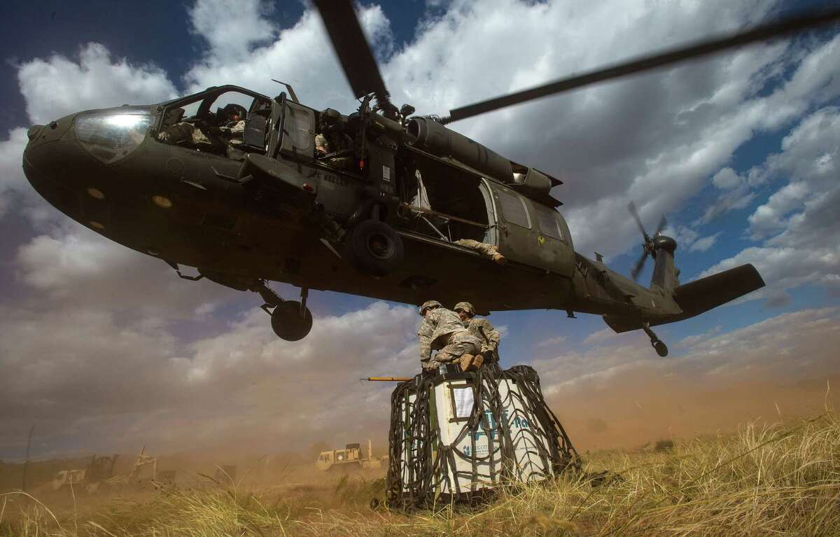 Soldiers battle the wind as a Sikorsky UH-60 Black Hawk flies lower so they can attach supplies during training at Fort Carson in Colorado Springs. Lockheed Martin is adding a business line with its Sikorsky deal. Aircraft.