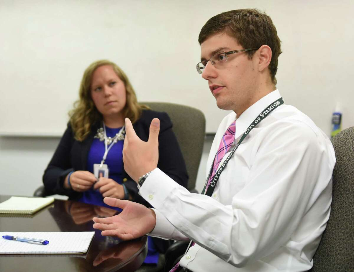 Outgoing Special Assistant to the Mayor Tom Dec and his successor Libby Carlson talk at the Government Center in downtown Stamford, Conn. Wednesday, July 15, 2015. Dec will be leaving his position at the end of the month at which point Carlson will take over.