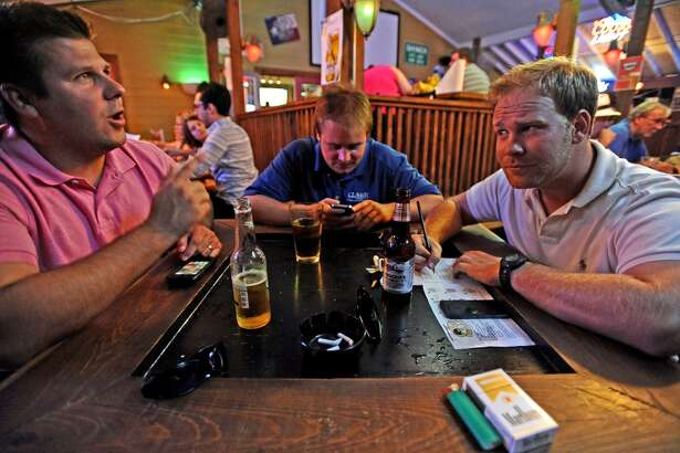 From left to right; Daniel Walker, John Worthington, and Matt Hendon play Geeks Who Drink trivia game on Tuesday, July 2, 2013, at Luke's. Photo taken: Randy Edwards/The Enterprise