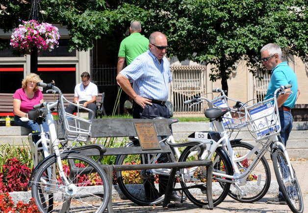 Louis Klender of Latham, left, and Wendall Thayer of Voorheesville, right, look over some of the City's Bikeshare Week bicycles available to share Monday, Aug. 11, 2014, at Tricentennial Square in Albany, N.Y.  (Will Waldron/Times Union archive)