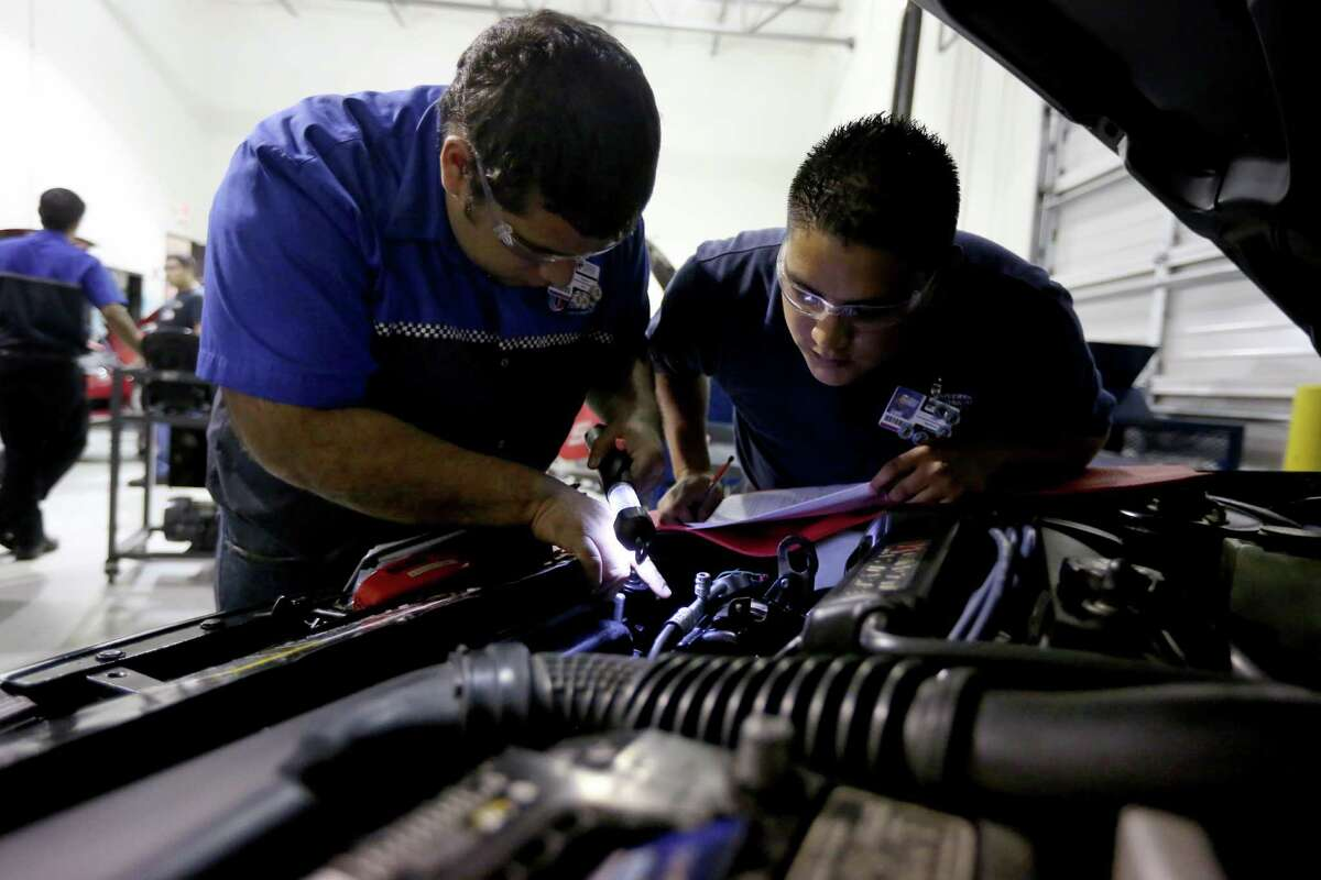 Students Sotero Neri, left, and Jose Martinez check for leaks in a car's air-conditioning system at Universal Technical Institute.