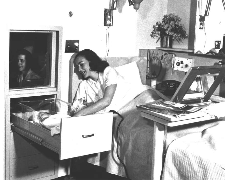 "The famous ""baby in the drawer"". It was an early efficiency item: the nursery was on the other side of the wall from the mother's bed. The babies lay in crib-like drawers, where nurses would care for them. This photo was taken in Walnut Creek. Photo: Kaiser Permanente, Courtesy"