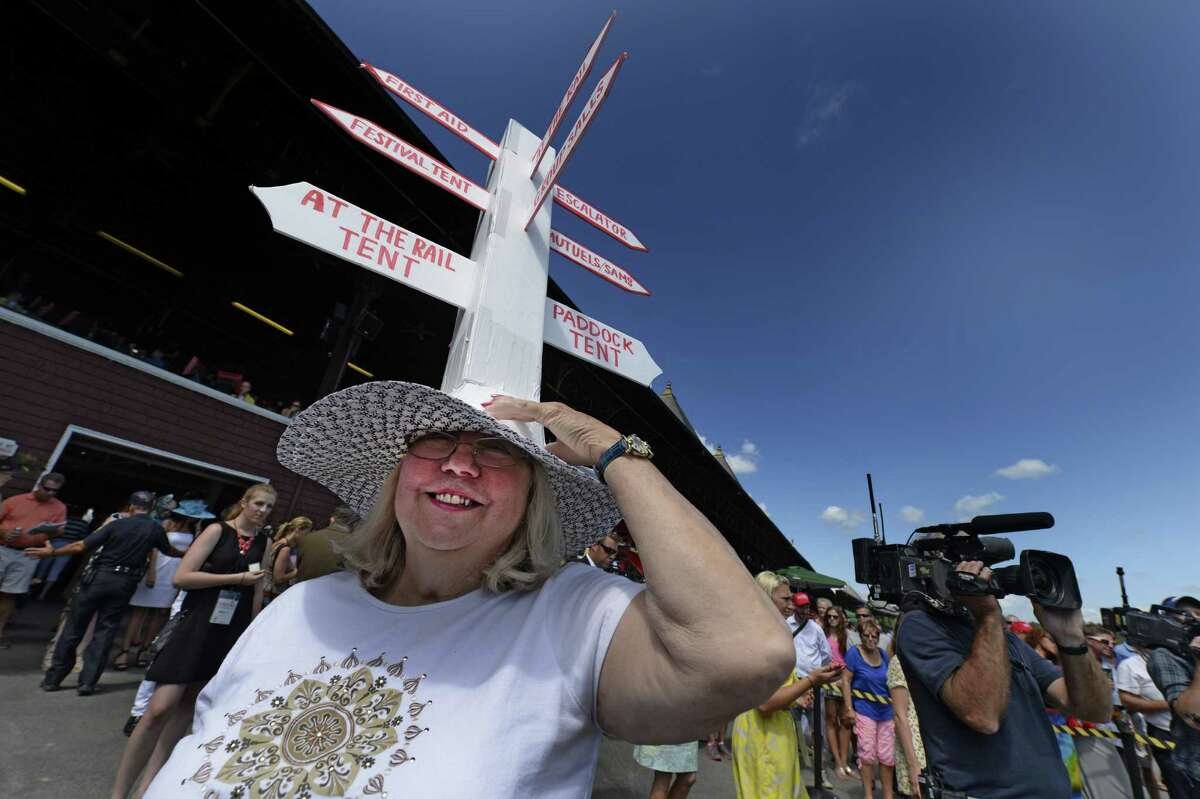Hat contest entrant Barbara Leyden holds her very tall hat from falling off before the judges get a chance to see her creation Sunday afternoon July 20, 2014 at the Saratoga Race Course in Saratoga Springs, N.Y. (Skip Dickstein / Times Union) ORG XMIT: MER2015070711501223