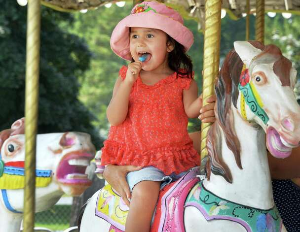Three-year-old Isabella Molina of Halfmoon rides the Merry-go-round on opening day of the Saratoga County Fair Tuesday July 22, 2014, in Ballston Spa, NY.  (John Carl D'Annibale / Times Union) ORG XMIT: MER2015070712051186 Photo: John Carl D'Annibale / 00027870A