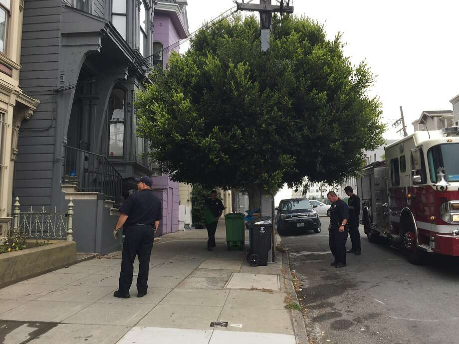 Firefighters clean up blood left behind when a U.S. Mint police officer shot Blue, an 11-month-old pit bull, outside Blue's home near San Francisco's Duboce Triangle neighborhood on Tuesday, July 21, 2015. Photo: Vivian Ho, San Francisco Chronicle