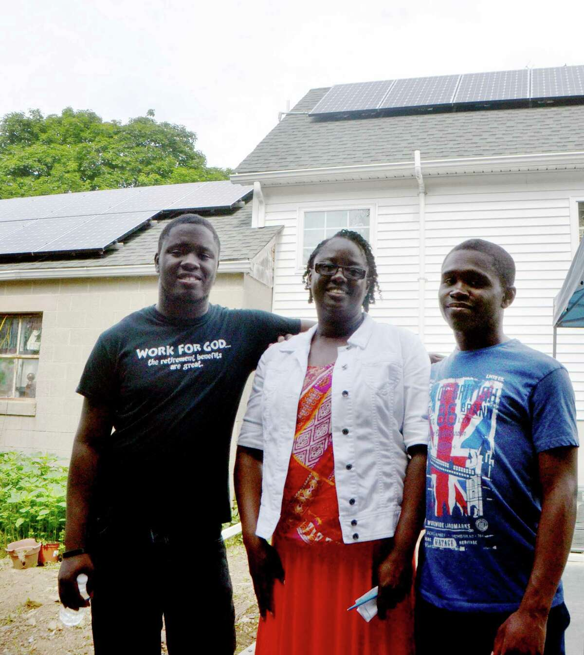 Susan Young and her sons, twenty-two year old Jason and seventeen-year old Shawn, pose in front of the solar panels on their home in Bridgeport, Conn. on Tuesday, July 21, 2015. The Young's installation of solar power, as well as other energy efficiency measures, are financed through a public-private partnership between the Connecticut Green Bank and PosiGen and contribute 80-90% of their energy usage.