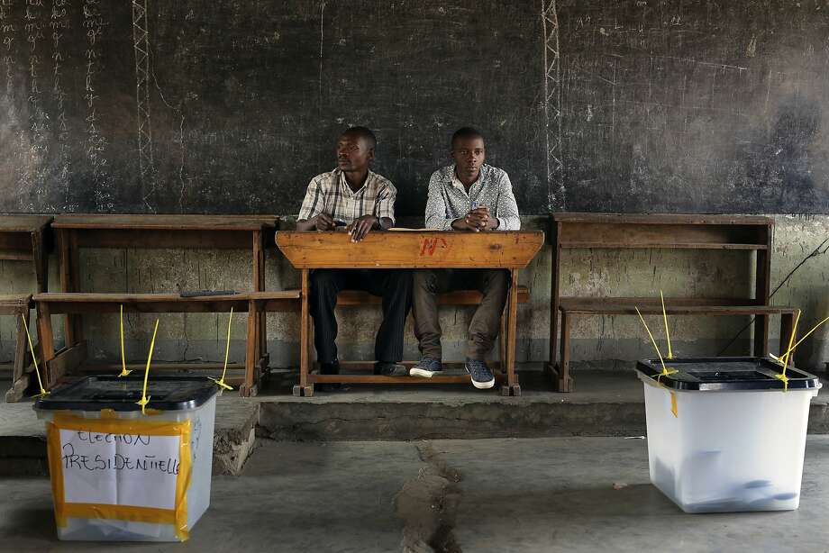 Election observers sit in an empty polling station for the presidential elections in Bujumbura, Burundi, Tuesday, July 21, 2015. A low turnout was experienced in several polling stations in the Burundi's capital at the start of voting in the country's presidential election following a night of explosions and gunfire in at least two opposition strongholds that oppose President Pierre Nkurunziza's candidacy for a third term in office. (AP Photo/Jerome Delay) Photo: Jerome Delay, Associated Press