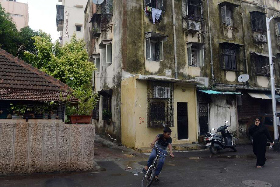 Pedestrians pass by the former residence of Yakub Memon, a plotter of the 1993 Mumbai bomb blasts that killed 257 in 1993. Photo: Indranil Mukherjee, AFP / Getty Images
