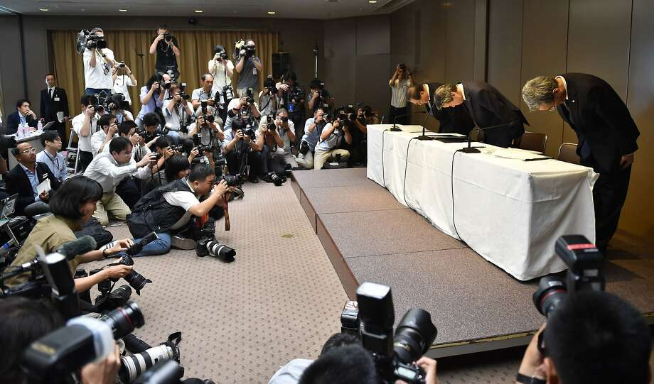 CEO Hisao Tanaka (center), bows at a news conference with Chairman Masashi Muromachi (left) and executive Vice President Keizo Maeda. Photo: Kazuhiro Nogi, AFP / Getty Images