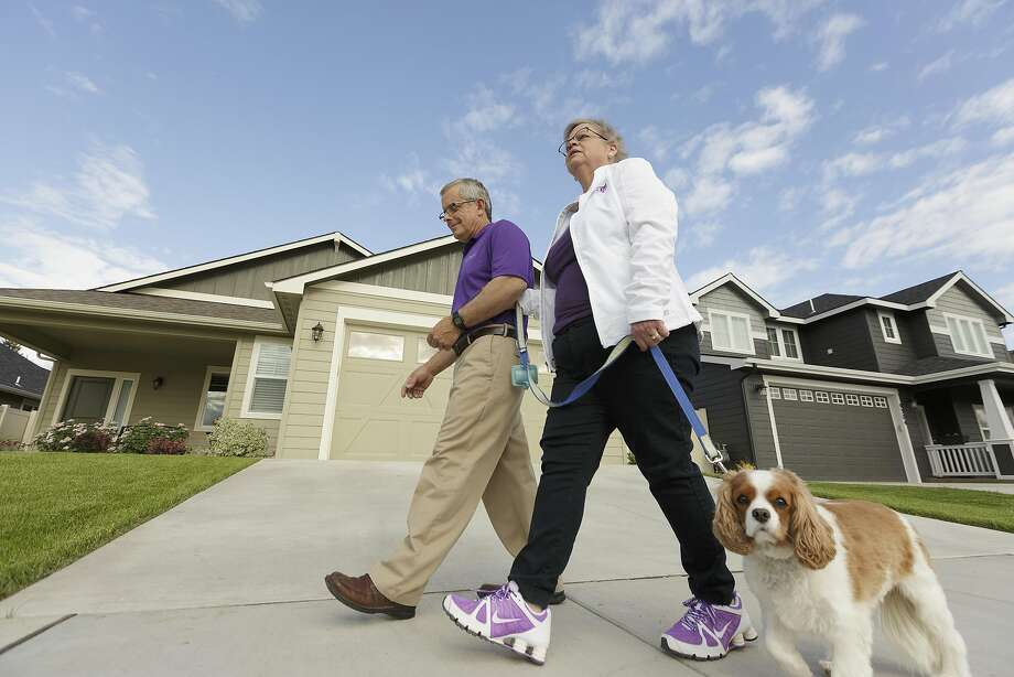 Amy Shives, right, and her husband, George, walk their cavalier King Charles spaniel Chester in their neighborhood, Wednesday, June 3, 2015, in Spokane, Wash. Amy Shives was diagnosed with early onset Alzheimer's disease in 2011 and has since been involved with the Alzheimer's Association. Nearly two-thirds of Americans with Alzheimer's disease are women, and now some scientists are questioning the long-held assumption that it's just because women tend to live longer than men. Photo: Young Kwak, Associated Press