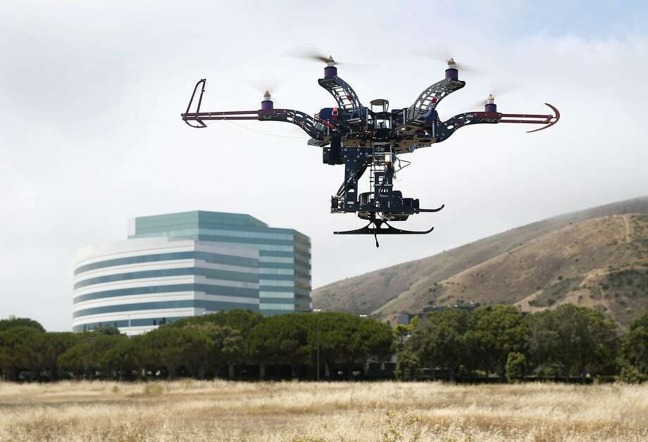 "Jason Lam, founder of AeriCam Hollywood, pilots a six propellor ""hexicopter"" in a demonstration flight at Sierra Point in Brisbane, Calif. on Tuesday, July 21, 2015. Officials are seeking authorization to disable drones that block the flight path of firefighting aircraft that make water drops above wild fires. Photo: Paul Chinn, The Chronicle"