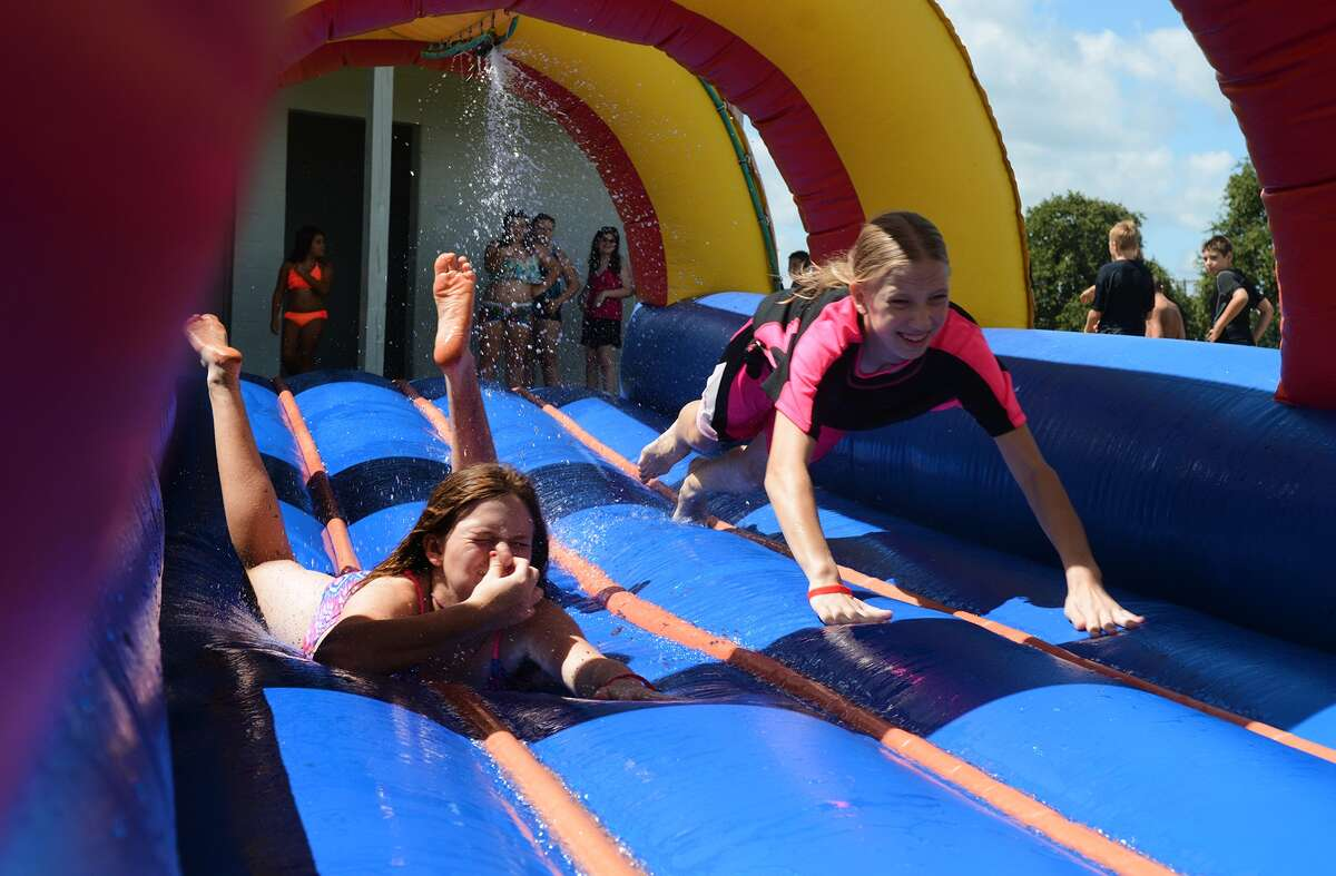 Jordan Jones, 12, left, a 7th grader at McCullough Junior High, and Natalia Salivia, 12, a 7th grader at Knox Jr. High, team up on a water slide during the Conroe ISD Police Activity League summer camp program picnic at Lake Conroe Park on Friday, July 17, 2015. (Photo by Jerry Baker/Freelance)
