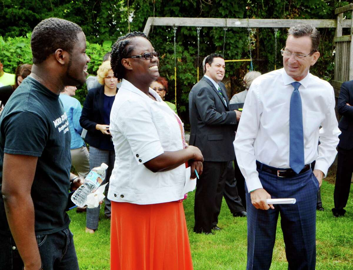 Susan Young and her son, Jason talk with Gov. Dannel Malloy before he spoke at her home in Bridgeport, Conn. on the partnership between The Connecticut Green Bank and PosiGen that provides incentive for homeowners that participate in their energy-saving program. The event, held in Young's backyard on Tuesday, July 21, 2015, highlighted the benefits her own household has seen by installing solar and other energy efficiency measures.