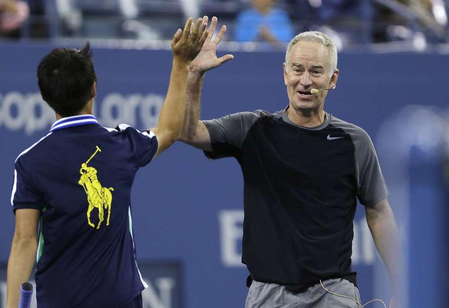 FILE - In this Sept. 4, 2014, file photo, John McEnroe high-fives a ball boy during an exhibition match prior to the quarterfinal between Roger Federer and Gael Monfils at the U.S. Open tennis tournament  in New York. John McEnroe says he's almost done playing competitive tennis. The 56-year-old Hall of Famer plans to play an exhibition match against Jim Courier next month in New Haven. That will be part of a Legends Event designed to increase attendance at the Connecticut Open, the last women's tournament before the U.S. Open. McEnroe told reporters on a conference call Tuesday, July 21, 2015,  the match is probably the last chance fans in Connecticut will have to see him play competitively. (AP Photo/Charles Krupa, File) Photo: Charles Krupa, Associated Press