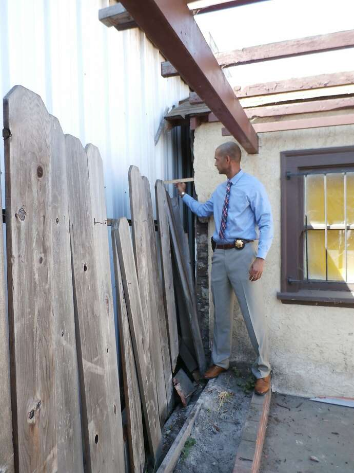 An Oakland police officer holds a ruler up to show the width of a gap between two buildings. Police said a man, identified as Richard Linyard by family members, who was allegedly fleeing from officers after a traffic stop died after becoming wedged between the buildings on July 19, 2015. Photo: Oakland Police Department
