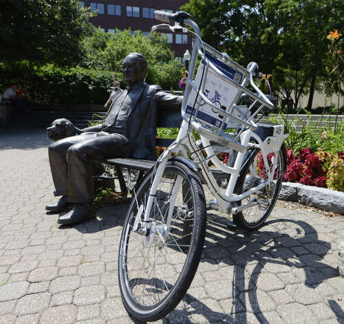 One of the bicycles available to share during the City's Bikeshare Week is locked to a bench next to a sculpture of Mayor Thomas Whalen III Monday, Aug. 11, 2014, at Tricentennial Square in Albany, N.Y. (Will Waldron/Times Union archive)