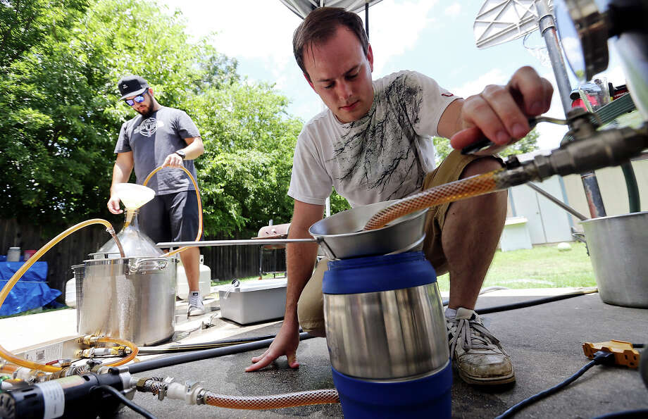 Jeff Weihe (right) monitors the flow of the wort - or pre-fermented beer - to the fermenter as co-founder Tim Castaneda fills the fermenter with the cooled wort. Photo: Edward A. Ornelas /San Antonio Express-News / © 2015 San Antonio Express-News