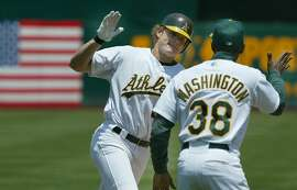 athletics103_mac.jpg  A's 22- Eric Byrnes rounds 3rd base and gives a high-five to Ron Washington after a 3 run homer in the 4th inning. Oakland Athletics Vs. Texas Rangers.6/19/03 in Oakland.  MICHAEL MACOR / The Chronicle