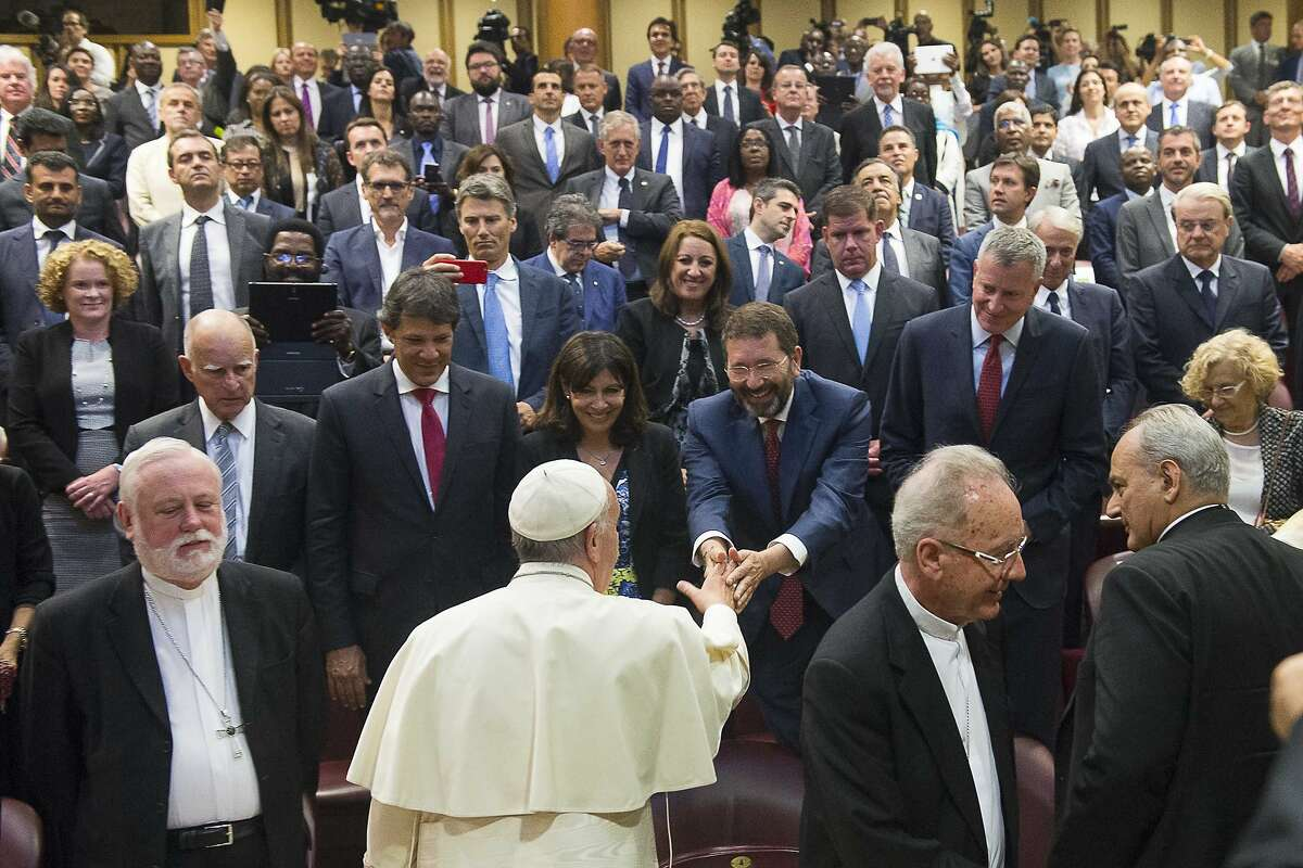 Pope Francis greets Rome Mayor Ignazio Marino as he meets mayors gathered in the Synod Hall during a conference on Modern Slavery and Climate Change at the Vatican, Tuesday, July 21, 2015. Dozens of environmentally friendly mayors from around the world are meeting at the Vatican this week to bask in the star power of eco-Pope Francis and commit to reducing global warming and helping the urban poor deal with its effects. Next to Marino, at left, is Paris Mayor Anne Hidalgo, at his right is New York Mayor Bill de Blasio and between the two, one row back is Boston Mayor Marty Walsh. (AP Photo/L'Ossservatore Romano, Pool)