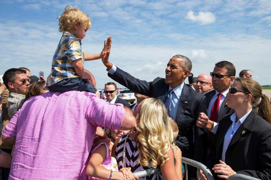 President Barack Obama is greeted by Elliot Riley, 2,of Cranberry Township, Pa., after the commander in chief arrived in Coraopolis, Pa., to speak at the VFW National Convention.  Photo: Evan Vucci, STF / AP