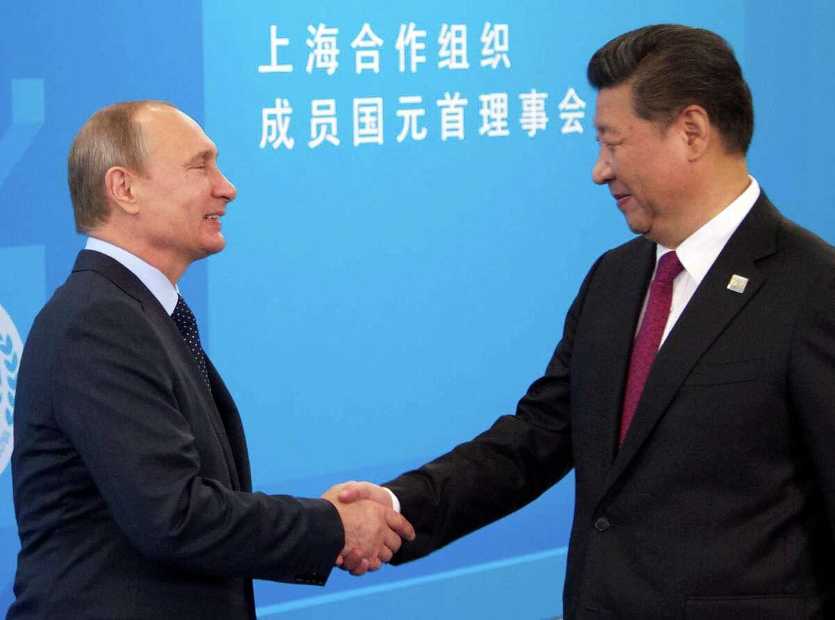 Russian President Vladimir Putin, left, shakes hands with China's President Xi Jinping prior the SCO (Shanghai Cooperation Organization) summit in Ufa, Russia, Friday, July 10, 2015. (AP Photo/Ivan Sekretarev)
