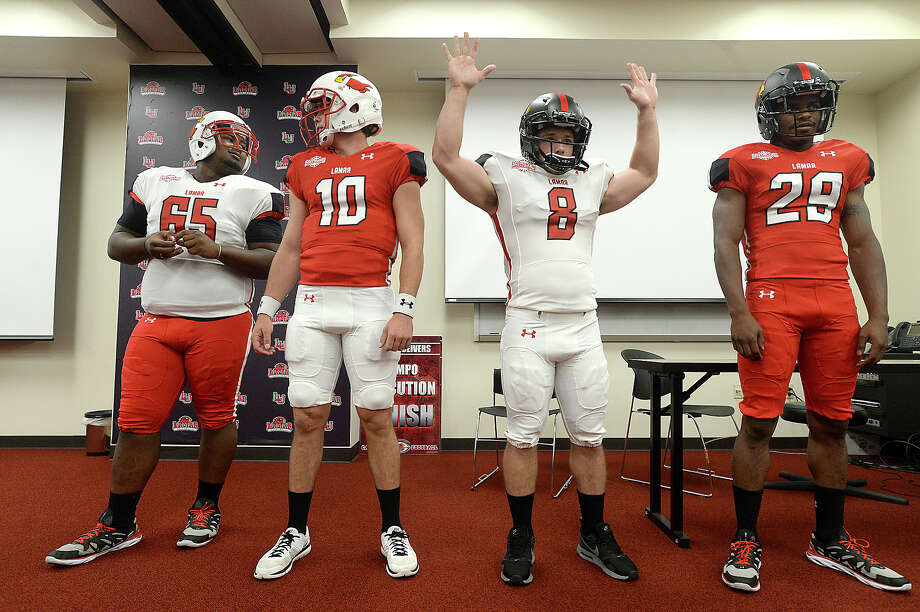 Kade Harrington shows the increased flexibility of his shirt as he and members of the Lamar University football team, including (from left) Omar Tebo, Joe Minden, and Xavier Bethany model the team's new uniforms during a press conference at the Dauphin Center Tuesday. Red and white and new white and black helmets will be worn in various combinations per head coach Ray Woodard's choice throughout the season.