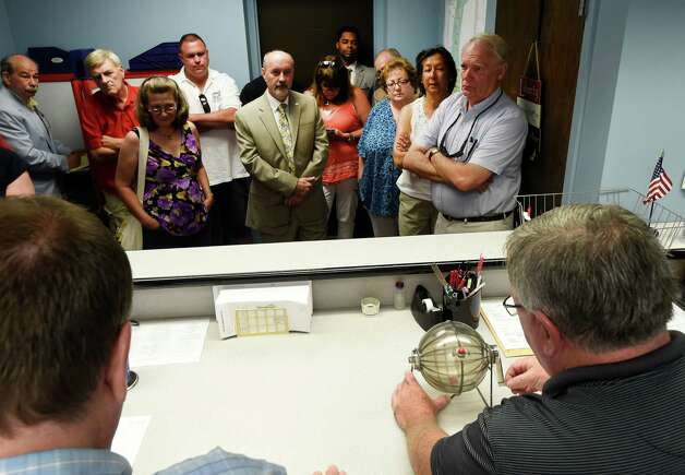 Kevin O'Mally, foreground right pulls the numbered balls from a shaker under the supervision of Ed McDonough and other Board members Tuesday morning July 21, 2015,  during the selection of the location of the positions on the primary ballot at the Board of Elections in Troy, N.Y.      (Skip Dickstein/Times Union) Photo: SKIP DICKSTEIN / 00032689A