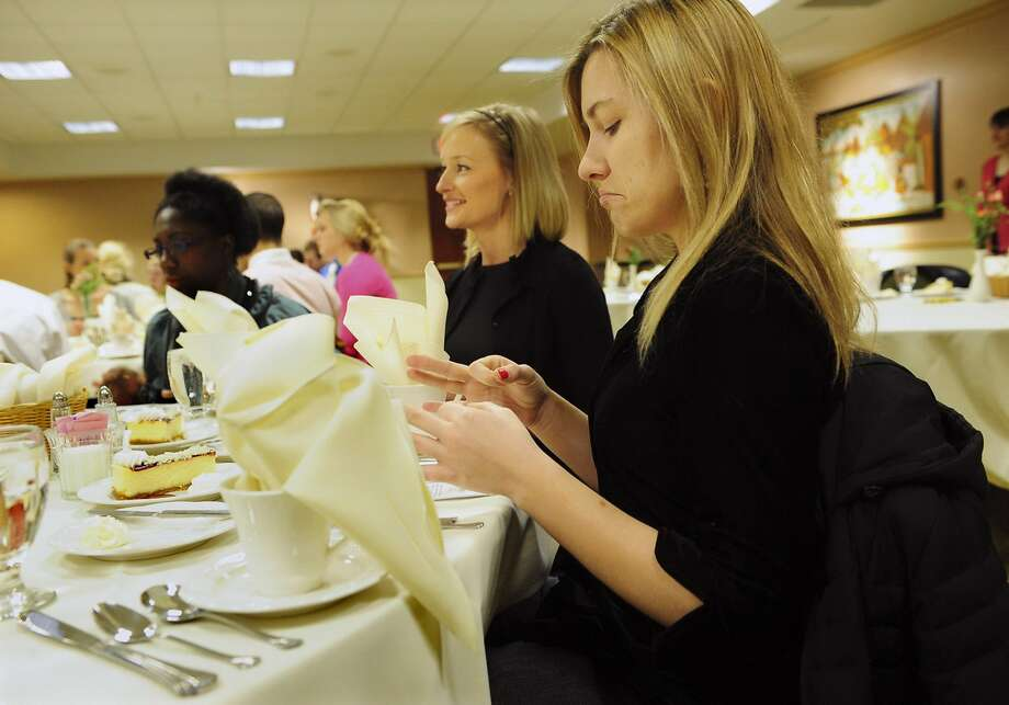 Duquesne University students Kim Firko, center, and Tatiana Duffey, right, do finger exercises during a class on the etiquette of consuming a four-course meal in March 2009 in Pittsburgh, Pa. More than 65 percent of business is conducted over a meal. (John Heller/Pittsburgh Post-Gazette/TNS) Photo: John Heller, McClatchy-Tribune News Service