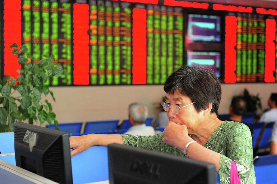 An investor observes stock market at a stock exchange hall earlier this month in Fuyang, Anhui Province of China. In recent weeks, the Chinese government has suspended trade in some stocks and ordered state-owned brokerages and banks to invest $483 billion to prop up the Shanghai composite index, according to Bloomberg News. Photo: ChinaFotoPress / 2015 ChinaFotoPress