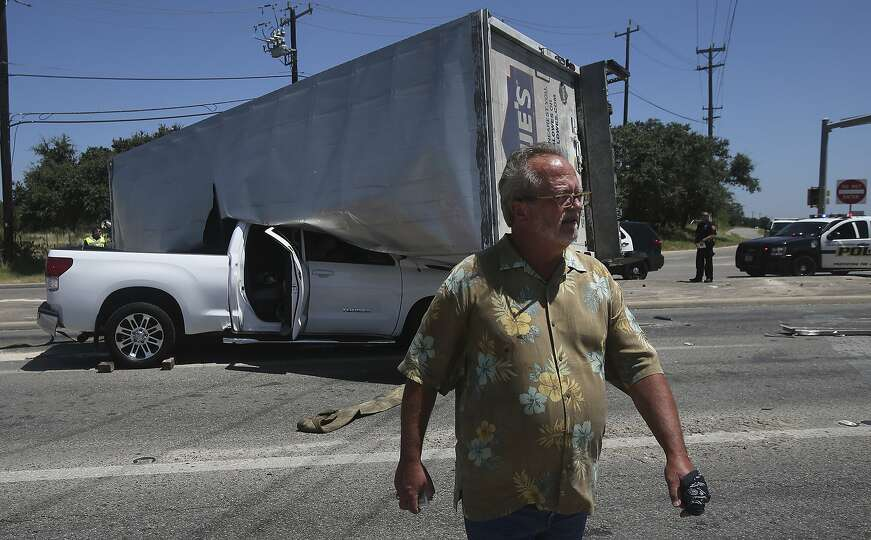 Dave Herndon,61, walks away from his crushed Toyota Tundra pickup truck Tuesday July 21, 2015 after