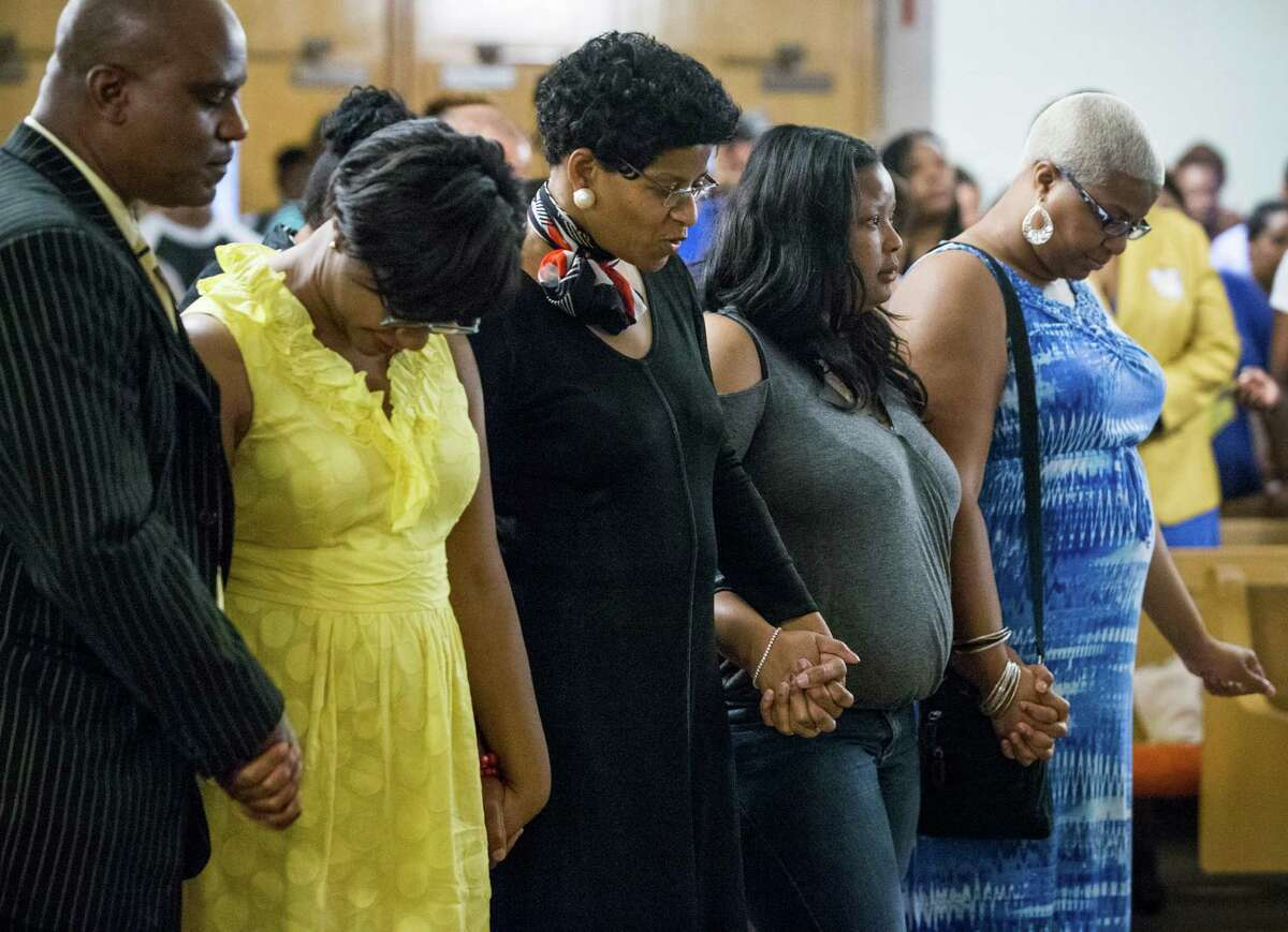Sandra Bland's family hold hands while they pray during a memorial service for Bland at All Faiths Chapel on the campus of Prairie View A&M University on Tuesday, July 21, 2015, in Houston. Bland, a 28-year-old African American woman, was arrested July 10, after being stopped by a Department of Public Safety trooper for failing to signal a lane change. A DPS spokesman said she was arrested after becoming
