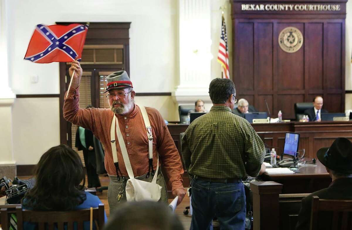 Bill Manuel waves a Confederate flag in front of Cassandra Littlejohn, a member of the NAACP, after he spoke in favor a keeping Confederate symbols on certain historical markers in Bexar County, as Bexar County Commissioners Court meets on Tuesday, July 21, 2015, to decide on the county's Confederate markers.