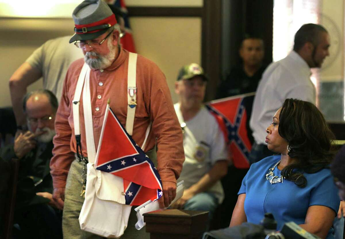 Cassandra Littlejohn, right, a member of the NAACP, watches as Bill Manuel, a member of the Sons of Confederate Veterans, walks forward to address Commissioners Court on Tuesday, July 21, 2015, where they were deciding about the county's Confederate markers, at the Bexar County Courthouse.