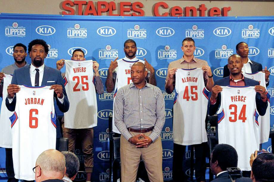 Clippers coach Doc Rivers, bottom right, helped welcome the team's recent signees, including DeAndre Jordan (6) and Josh Smith (behind Rivers). Photo: Nick Ut, STF / AP