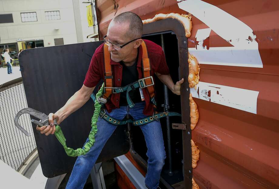 "Tim Hawkinson emerges from the huge shipping container which has been made into a giant bellows which by using wave action from the Bay creates the pressure to make the sounds through a converted bicycle, ""Bosun's Bass"" an art installation by Hawkinson  which is on display at the Exploratorium in San Francisco, Calif., as seen on Tues. July 21, 2015. Los Angeles artist Tim Hawkinson installs a big new commissioned public art installation at the Exploratorium, ""Bosun's Bass,"" a tide- activated sound work that evokes the bosun's pipe whistle used by mariners. It's part of the museums' ""Over the Water"" series. Photo: Michael Macor, The Chronicle"