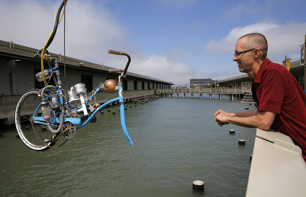 """Artist Tim Hawkinson, converted a bicycle that makes the different pitches of sounds of a Bosun's whistle, which hangs out over the water which is on display at the Exploratorium in San Francisco, Calif., as seen on Tues. July 21, 2015. Los Angeles artist Tim Hawkinson installs a big new commissioned public art installation at the Exploratorium, """"Bosun's Bass,"""" a tide- activated sound work that evokes the bosun's pipe whistle used by mariners. It's part of the museums' """"Over the Water"""" series."""