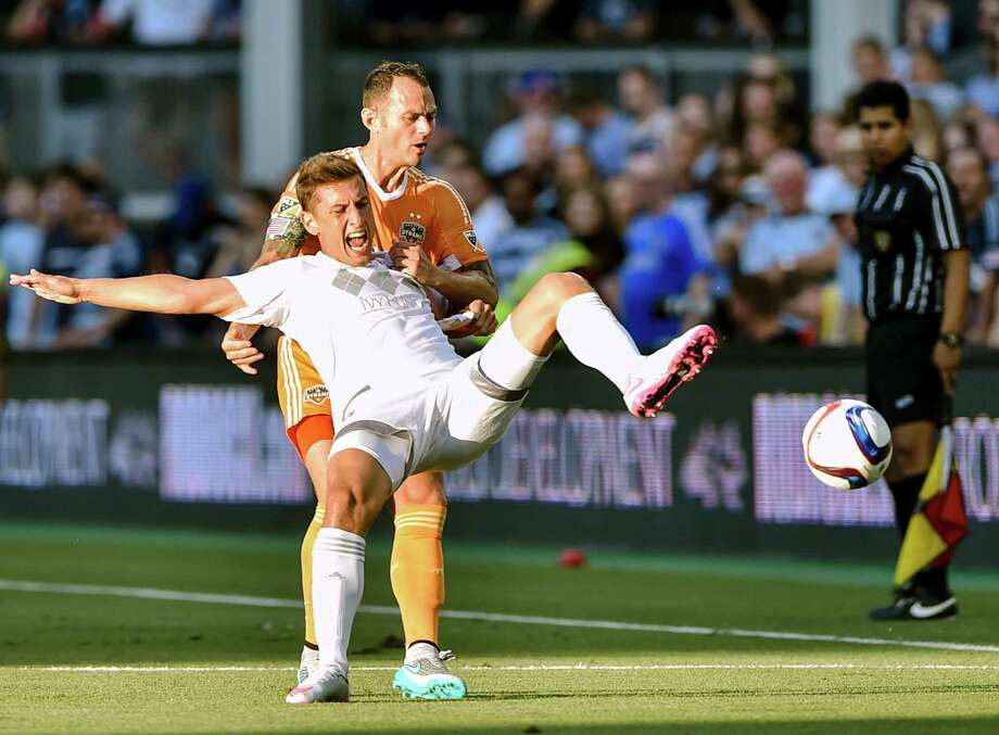 Dynamo midfielder Brad Davis, top, collides with Sporting Kansas City forward Krisztian Nemet. Photo: Allison Long, MBI / The Kansas City Star