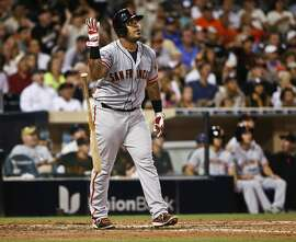 San Francisco Giants' Hector Sanchez flips away his bat a she watches his grand slam against the San Diego Padres during the sixth inning of a baseball game Tuesday, July 21, 2015, in San Diego. The Padres had intentionally walked Gregor Blanco to pitch to Sanchez. (AP Photo/Lenny Ignelzi)