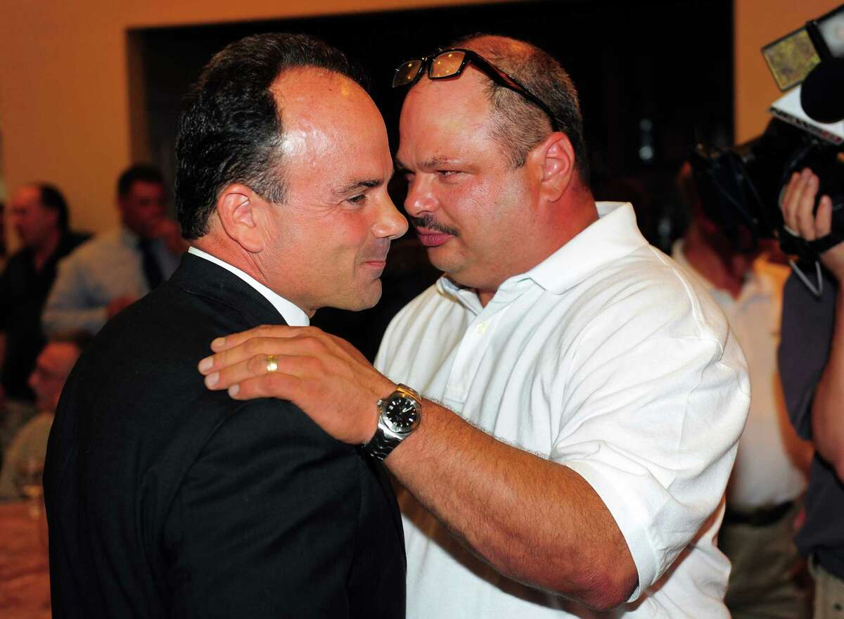 Former Bridgeport Mayor, Joseph Ganim, left, talks with former Bridgeport City Council member Richard Paoletto, during a meeting of the Bridgeport Democratic Town Committee at Testo's Restaurant in Bridgeport, Conn., on Tuesday July 21, 2015. The nomination for mayor was a fierce competition between current Mayor Bill Finch and former Mayor Joseph Ganim. The vote was fairly close, 49-41.