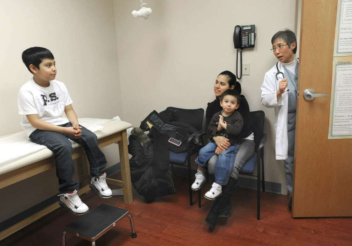 Dr. Pamela Paulhus, right, peeks in on Axel Ortiz,9, with his mother Nayeli and brother Danny, 3, at the Samaritan Health Center. Danny is being treated for asthma.