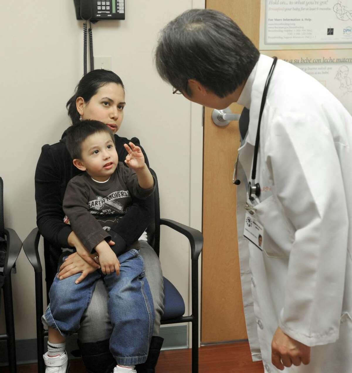 Dr. Pamela Paulhus takes a minute to chat with Danny Ortiz, 3, and his mother Nayeli. They are visiting the Samaritan Health Center in Danbury to get treatment for Danny's brother Axel's asthma.